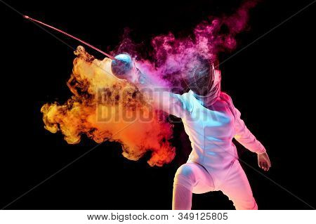 Contrasts. Teen Girl In Fencing Costume With Sword In Hand Isolated On Black Background, Neon Lighte