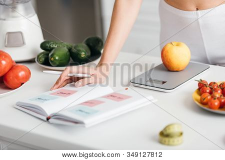 Selective Focus Of Woman Writing Calories While Weighing Apple Near Fresh Vegetables On Kitchen Tabl