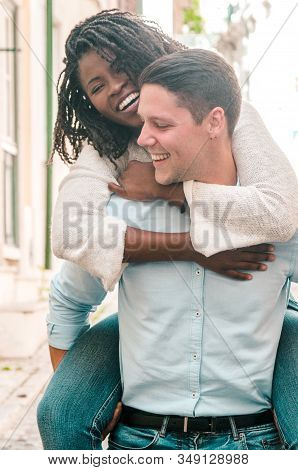 Playful Young Man Carrying Girlfriend On Back Outdoors. Happy Interracial Couple In Street. Romance