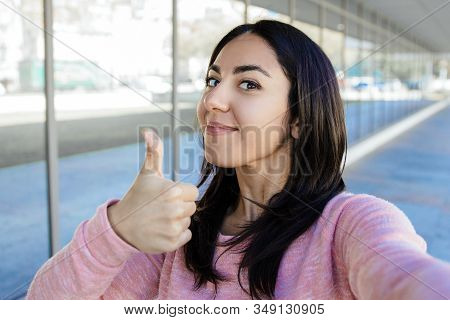 Positive Woman Taking Selfie Photo And Showing Thumb Up Outdoors. Pretty Young Lady Looking At Camer