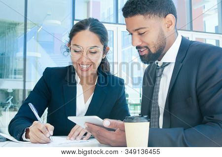 Smiling Business People Working And Using Tablet In Outdoor Cafe. Business Man And Woman Wearing For