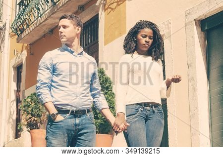 Bored Disappointed African American Girl Holding Hand Of Her Caucasian Boyfriend. Interracial Couple