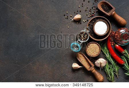 Various Spices And Herbs On A Stone Table. Top View With Copy Space.