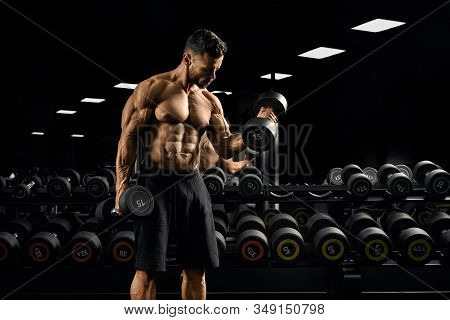 Front View Of Shirtless Bodybuilder Training Biceps With Weights Near Stand With Dumbbells. Portrait