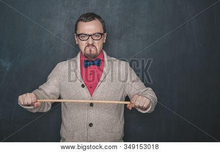 Angry Business Man Or Teacher With Pointer On Blackboard