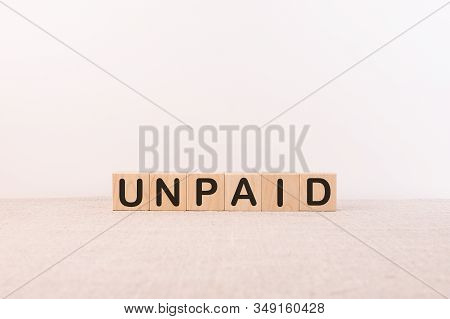 Unpaid Word From Building Blocks On A Light Background