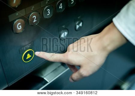Male Forefinger Pressing On Emergency Stop And Alarm Button In Elevator (lift). Mechanical Engineeri