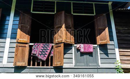 Batik Fabric Hanging On The Window Of Rumah Kampung Under The Bright Sunlight.