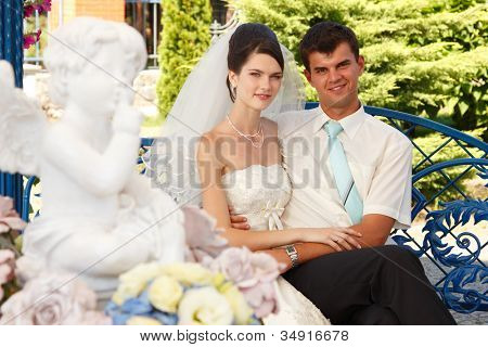 beautiful young bride with groom and statue of angel in front view