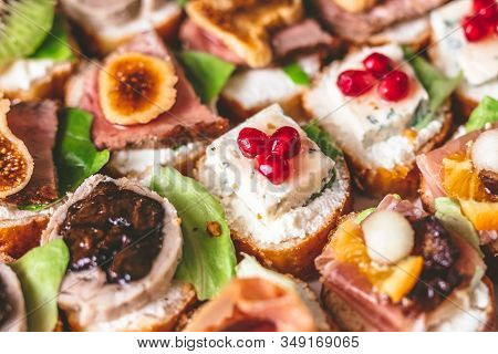 Crostini With Meat, Fruits, Vegetables And Cheese Close Up On Table.