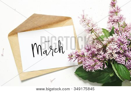 Inscription Hello March. Lilac Flowers And Envelope On White Background. Spring Flowers. Top View, F