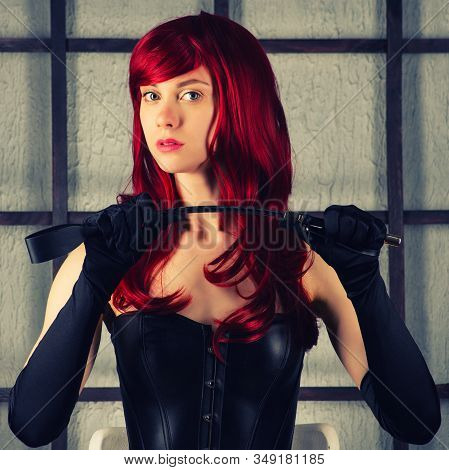 Red-haired Girl In A Leather Corset Holds Spank. Bdsm Outfit. Toned