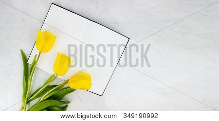 Colorful Bouquet Of Yellow Tulips And Sketchbook, Notebook Flat Lay On Marble Background Top View Wi