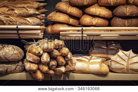 Loaves Of Bread On Wooden Shelves In Baker Shop, In Germany. Different Types Of Bread. Tasty Sourdou