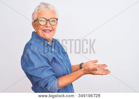 Senior grey-haired woman wearing denim shirt and glasses over isolated white background pointing aside with hands open palms showing copy space, presenting advertisement smiling excited happy