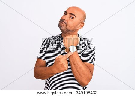 Middle age handsome man wearing striped navy t-shirt over isolated white background In hurry pointing to watch time, impatience, looking at the camera with relaxed expression