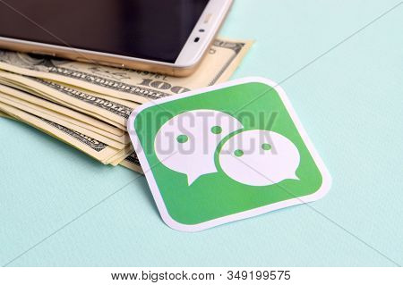 Wechat Paper Logo Lies With Envelope Full Of Dollar Bills And Smartphone
