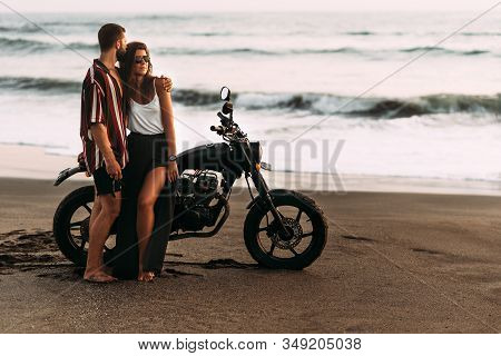 Couple On A Motorcycle On The Beach. A Couple In Love On The Beach Meets The Sunset. A Man Embraces