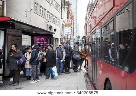 People Of All Ages Are Waiting For A Bus At A Stop Near Liverpool Street.