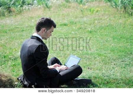 Business man with laptop in nature