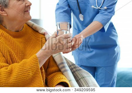 Care Worker Giving Water To Elderly Woman In Geriatric Hospice, Closeup