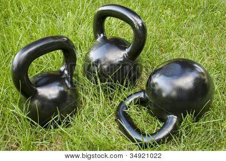 three heavy iron  kettlebells in green grass - outdoor fitness concept