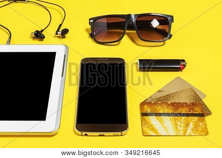 Tablet Pc, Smartphone Earphones, Cigarette Lighter, Sock, Sunglasses And A Gold Bank Cards Lying On