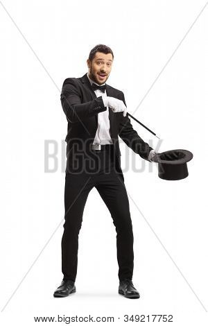 Full length shot of a magician making a magic trick with a wand and a tophat and looking at the camera isolated on white background