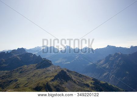 View At The Swiss Alps In Summer With Snow Covered Mountains In The Background