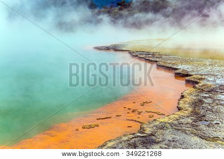 Thermal Wonderland of hot waters is Wai - O - Tapu. New Zealand, North Island. Picturesque lake of multicolored thermal waters evaporates in the air. The concept of active and phototourism