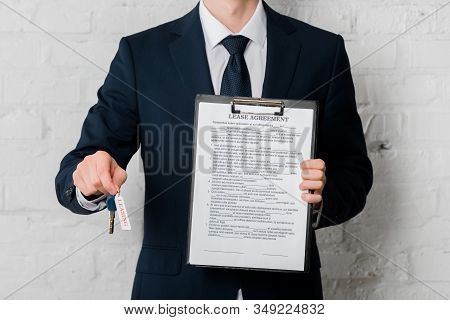 Cropped View Of Realtor In Suit Holding Key With Leasing Lettering And Clipboard With Lease Agreemen