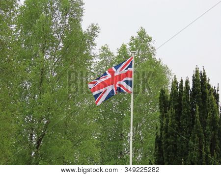 British Flag Waving In Wind On A Rainy Spring Day, Budding Birch Trees, Some Evergreens. Ww1 Memoria