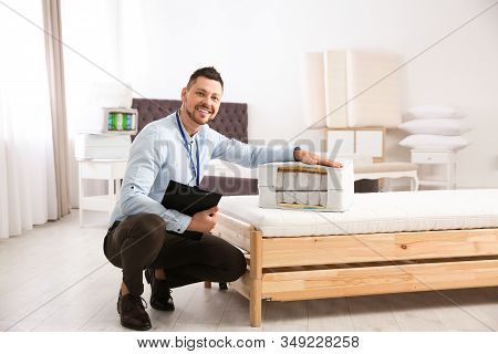 Salesman With Section Of Mattress In Furniture Store