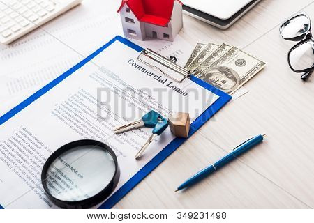 Document With Commercial Lease Lettering On Clipboard Near Keys, Money, House Model, Pen, Magnifier