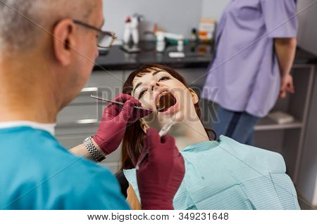 Young Pretty Woman Patient In Dental Clinic Having Dental Check And Treatment, Woman With Open Mouth