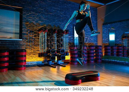 Shot Of Sporty Young Woman Using Step Platform At Gym. Aerobic And Fitness Exercises.