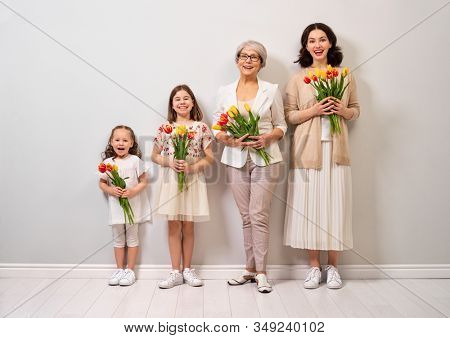 Happy women's day! Children daughters are congratulating mom and grandma giving them flowers tulips.Granny, mum and girls smiling on light grey background. Family holiday and togetherness.