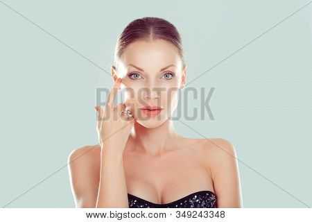 Beauty With Flawless Skin. Natural Brunette Model Posing Hand On Face Looking At Camera On Light Gre