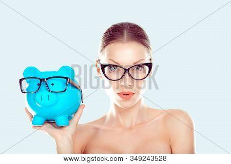 Glasses Sale Concept. Happy Woman Holding Piggy Bank Both Wearing Eye Wear Glasses. Female Model Iso