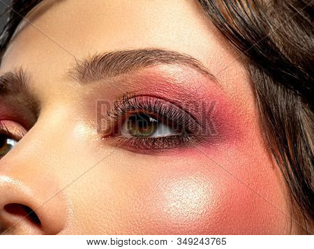 Bright makeup on a woman's eye. Bright red eye makeup. Macro shot of a woman's eye with cherry-colored blush. Colorful and vivid makeup. Fashionable eye make-up. Art. Trendy style.