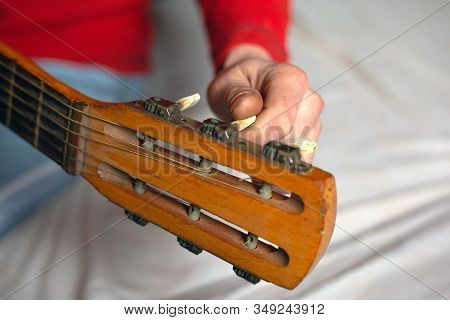 Tuning The Guitar, The Musician Hand Twists The Melodies Of The Guitar, Tuning The Instrument.