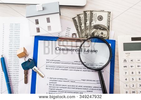 Top View Of Document With Commercial Lease Lettering On Clipboard Near Keys, Money, House Model, Pen