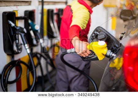 Yellow Oil Nozzle In Gas Station. Hands Refilling The Car With Fuel At The Gas  Station, Black Car I