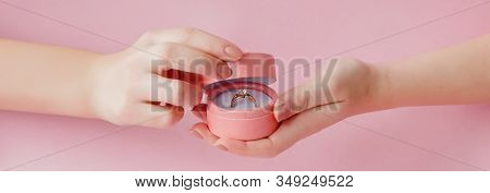 Woman Opens A Gift Box With Jewellery. Wedding Ring In A Box In The Hands Of Women On A Pink Backgro