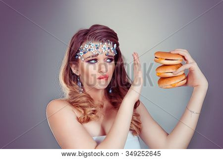 Diet Concept. Woman Has Craving For Fast Food In Her Hand, She Is Hardly Abstaining Avoiding To Eat