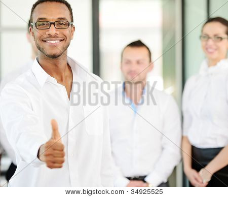 Business person giving you thumb up with colleagues in background