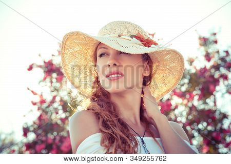 Daydreaming About Future. Pensive Beautiful Girl In Straw Hat Looking Up Smiling Slightly Holding To