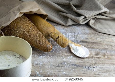 A Loaf Of Bread Along With Rocking For The Dough In A Craft Bag Stand On A Wooden Table, Next To It