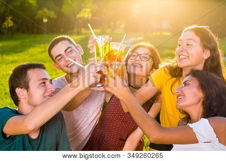 Young Friends Toasting With Cocktails In The Park.