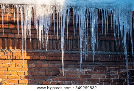 Large Icicles Hanging From The Roof Of An Old Brick Building. Roof Of Old Building Covered With Shar